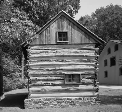 black and white photo of a colonial log cabin, one end with two windows but no doors