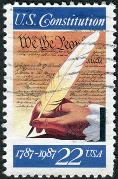a US stamp celebrating the centennial of the US Constitution; shows a hand holding a pen quill against a background of the Constitution
