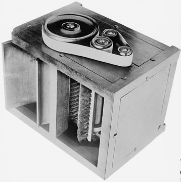 box-shaped machine with belts on top and an open side