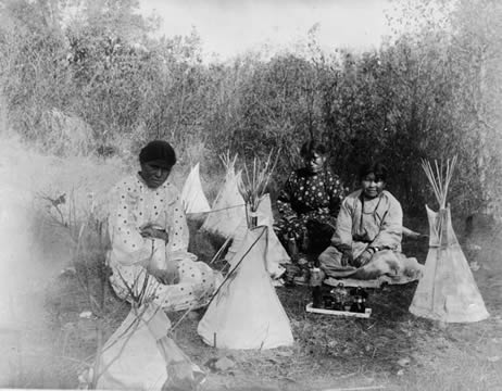 photograph of three young Indian girls playing with toy teepees