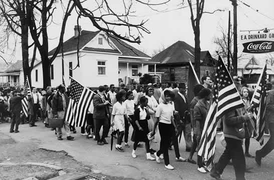 photograph of mainly Black men, women, and children marching peacefully with American flags back